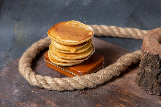 Front view of delicious pancakes with ropes on the grey surface