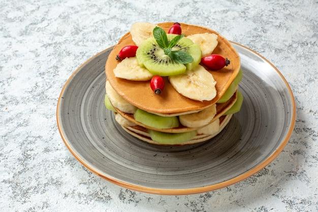 접시 안에 얇게 썬 과일과 함께 전면보기 맛있는 팬케이크