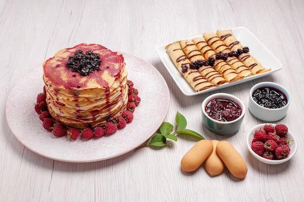 白いデスク パイ フルーツ ビスケット甘いケーキ ベリーにイチゴとゼリーの正面おいしいパンケーキ