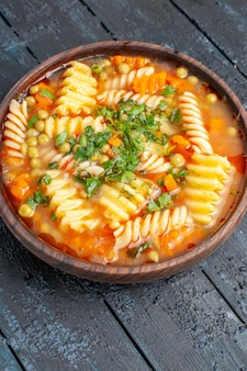 Vista frontale deliziosa zuppa di pasta di pasta italiana a spirale con verdure sul piatto da scrivania scuro zuppa di salsa di cena di pasta italiana