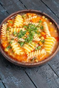 正面図ダークデスクディッシュにグリーンのスパイラルイタリアンパスタからのおいしいパスタスープイタリアンパスタディナーソーススープ