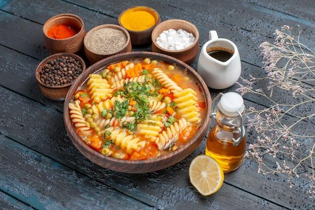 紺色の机にグリーンと調味料を添えた美味しいパスタスープディナー料理ソース料理イタリアンパスタスープ