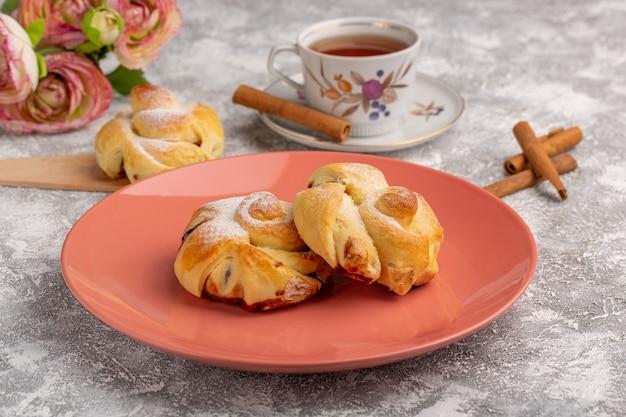 Вид спереди вкусная выпечка с начинкой внутри тарелки вместе с чаем и корицей на белом столе, фруктовый торт, выпечка, печенье