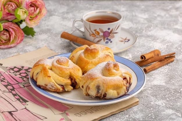 Вид спереди вкусная выпечка с начинкой внутри тарелки вместе с чаем и корицей на белом столе, сладкий сахарный торт, выпечка, фрукты