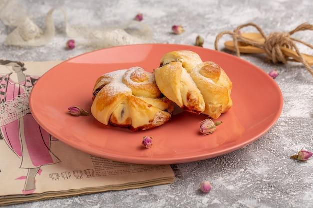 Вид спереди вкусная выпечка с начинкой внутри тарелки на белом столе, сладкая выпечка из сахарного торта