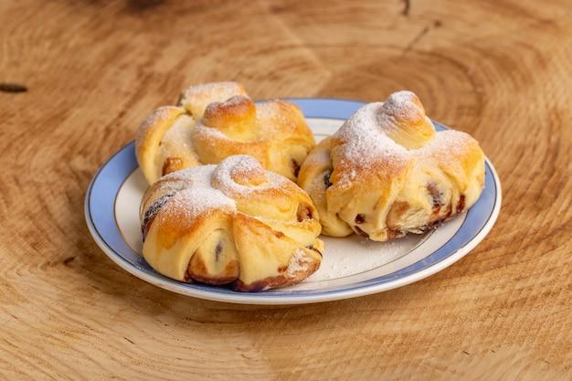 Вид спереди вкусная выпечка с начинкой внутри тарелки на деревянном столе, сладкий сахарный торт, выпечка, фрукты