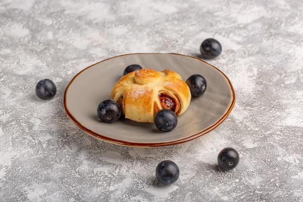 Vista frontale deliziosa pasticceria con ripieno insieme a prugnoli sul tavolo, dolce zucchero torta cuocere pasticceria frutta