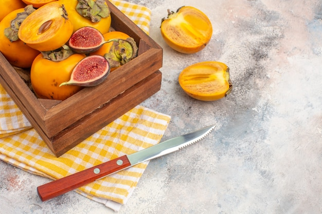 Front view delicious persimmons and cut figs in wood box yellow kitchen towel a knife on nude background free space