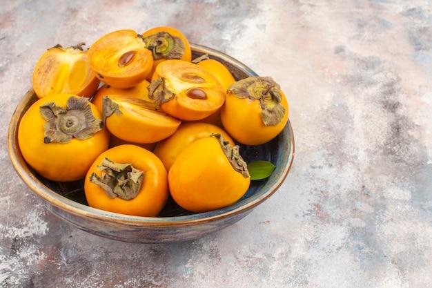 正面から見ると、空きスペースのあるヌードのボウルに美味しい柿が入っています。