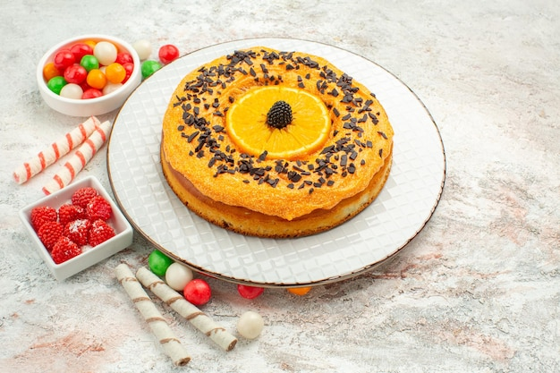 Front view delicious pie with colorful candies on white background pie biscuit sweet dessert rainbow