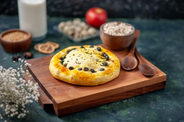 Vista frontale deliziosa torta con uova e latte su un forno da tè blu scuro torta di pasta dolce torta di colore hotcake