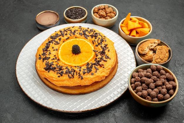 暗い背景のティービスケットフルーツデザートパイケーキにオレンジスライスと正面図おいしいパイ