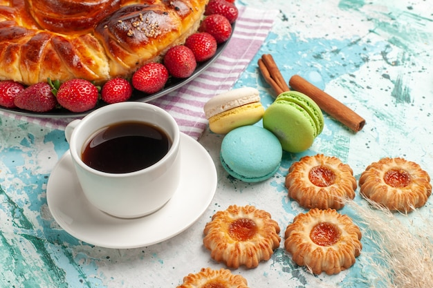 Vista frontale deliziosa torta con fragole macarons e tazza di tè sulla superficie blu torta biscotto dolce caramella torta biscotto