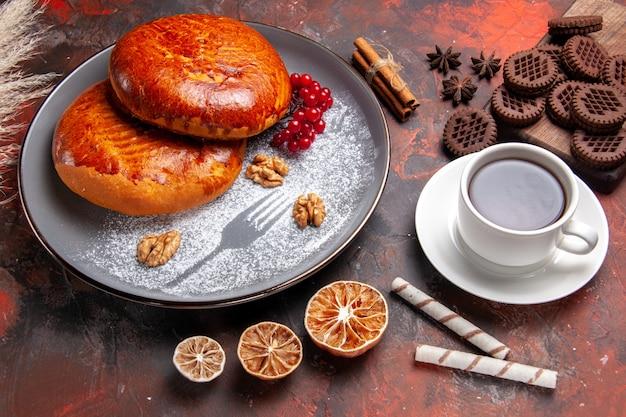 暗いテーブルの上のお茶とおいしいパイの正面図甘いパイペストリーケーキ