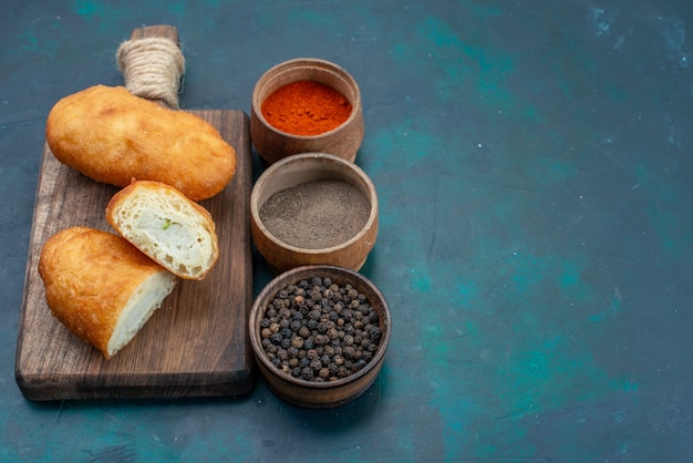 Vista frontale deliziose torte con ripieno di carne e condimenti sulla superficie blu scuro pasta torta pane panino cuocere cibo