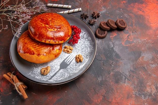 Vista frontale deliziose torte con bacche rosse sul tavolo scuro torta torta di pasticceria dolce