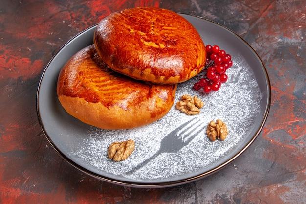 Vista frontale deliziose torte con bacche rosse sulla torta di torta di pasticceria dolce tavolo scuro