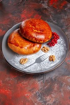 暗いテーブルの甘いペストリーパイケーキに赤いベリーと正面図おいしいパイ