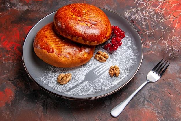 暗い机の上の赤いベリーとおいしいパイの正面図甘いパイケーキペストリー
