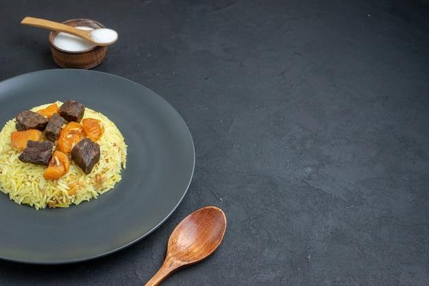 전면보기 맛있는 필라프는 어두운 표면에 고기 조각과 조미료로 밥을 요리했습니다.