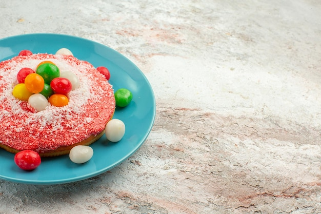 Вид спереди вкусный розовый торт с красочными конфетами внутри тарелки на белом фоне пирог цвета радуги торт десертные конфеты