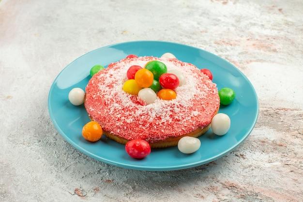 正面図白い背景の上のプレートの中にカラフルなキャンディーとおいしいピンクのケーキパイ虹色のケーキデザートキャンディー
