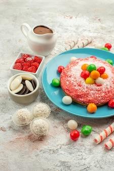 正面図白い背景の上のカラフルなキャンディーとおいしいピンクのケーキデザートグッディレインボーカラーケーキキャンディー