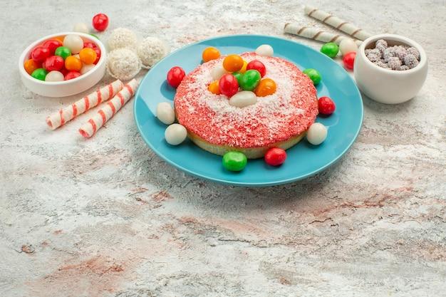 正面図白い背景の上のカラフルなキャンディーとおいしいピンクのケーキキャンディーデザートカラーレインボーグッディーケーキ