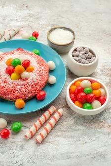 正面図白い背景の上のカラフルなキャンディーとおいしいピンクのケーキデザートカラーグッディレインボーケーキキャンディー