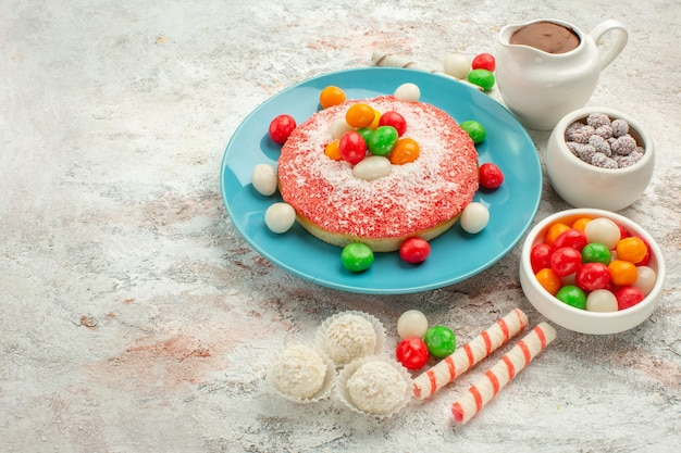 Front view delicious pink cake with colorful candies on white background dessert color rainbow candy cake goodie