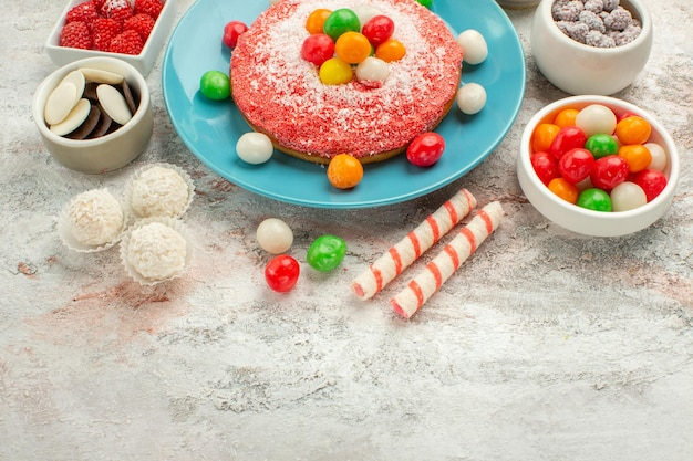 Front view delicious pink cake with colorful candies on white desk dessert goodie rainbow color cake candy
