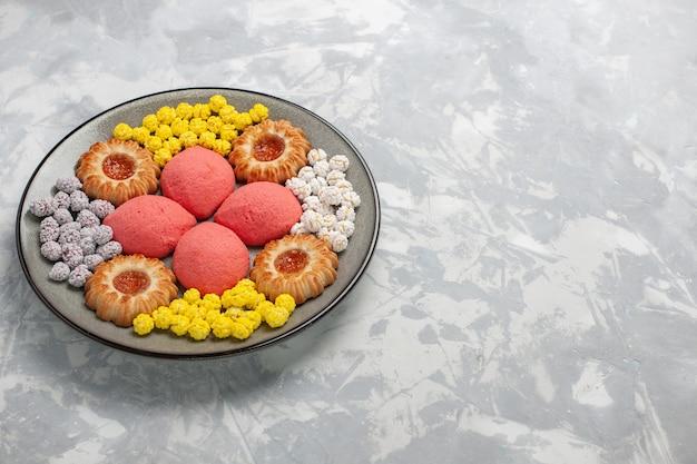 흰색 표면에 접시 안에 사탕과 쿠키와 전면보기 맛있는 핑크 케이크