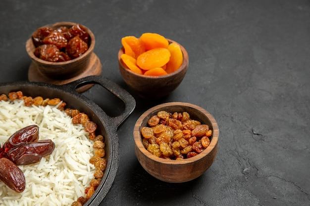 Vista frontale deliziosa farina di riso cucinata plov con uvetta sulla superficie scura cibo cena orientale pasto