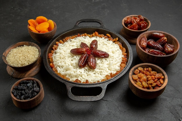 Front view delicious plov cooked rice meal with raisins on the dark surface food rice eastern dinner meal
