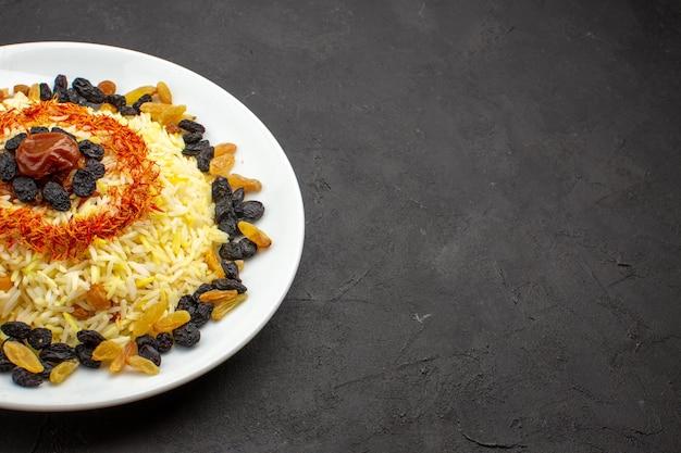 Вид спереди вкусный плов с маслом и изюмом внутри тарелки на темном пространстве