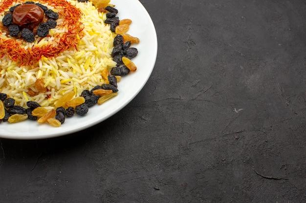 Вид спереди вкусный плов с маслом и изюмом внутри тарелки на темном столе