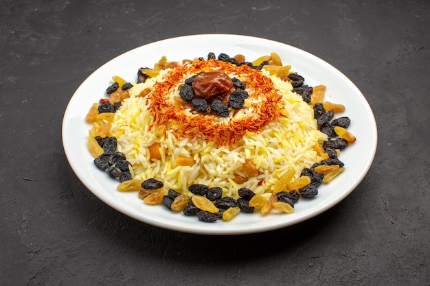 Front view delicious plov with oil and raisins inside plate on dark space