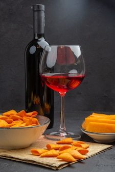 Front view of delicious potato chips inside and outside the bowl and red wine in a glass on an old newspaper bottle on ablack background
