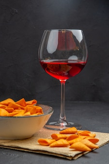 Vista frontale di deliziose patatine dentro e fuori la ciotola e vino rosso in un bicchiere su un vecchio giornale
