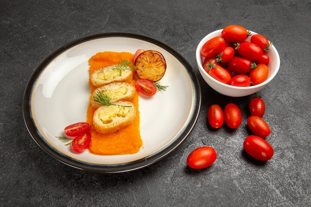 正面図濃い灰色の背景にカボチャとフレッシュトマトを添えたおいしいポテトパイオーブン焼き色皿ディナースライス