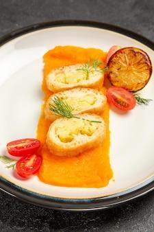 Vista frontale deliziose torte di patate con zucca all'interno del piatto sullo sfondo grigio scuro forno cuocere la fetta della cena del piatto di colore