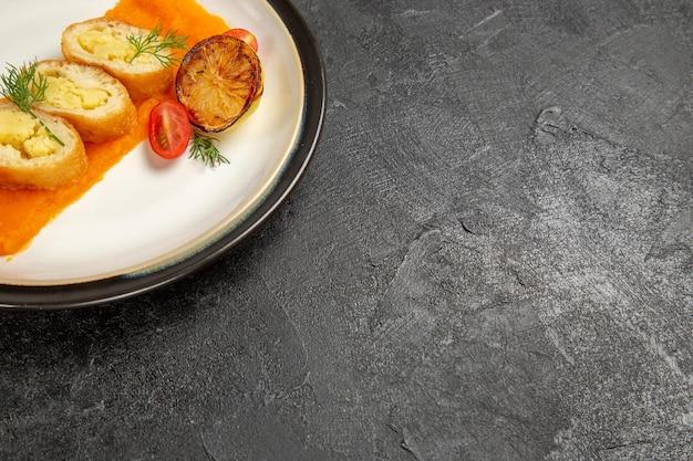 正面図ダークグレーの背景にカボチャの内側のプレートが付いたおいしいポテトパイオーブン焼き皿ディナースライス