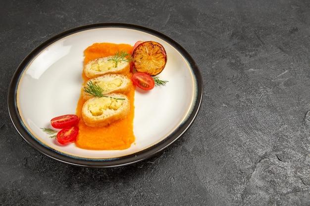 正面図ダークグレーの背景にカボチャの内側のプレートが付いたおいしいポテトパイオーブン焼き色皿ディナースライス