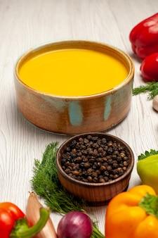 Вид спереди вкусный крем-суп из тыквы, текстурированный с овощами на белом столе, блюдо из спелого супа, соус для еды