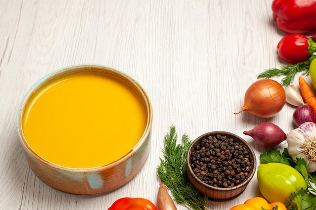 Front view delicious pumpkin soup cream textured with vegetables on a white desk ripe soup dish meal sauce
