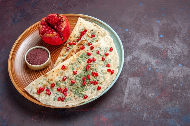 Vista frontale deliziosi qutab cotti pezzi di pasta con verdure e melograni su una superficie scura pasto di pasta per la cena