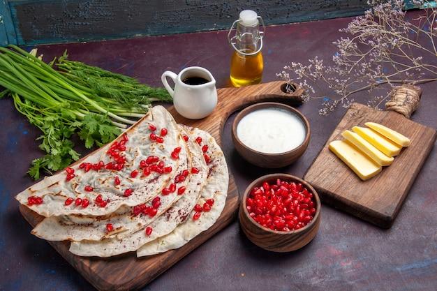 Вид спереди вкусные кутабс-питы с мясом, оливковым маслом и свежими гранатами на темной поверхности, тесто, лаваш, мясная мука, кондитерские изделия