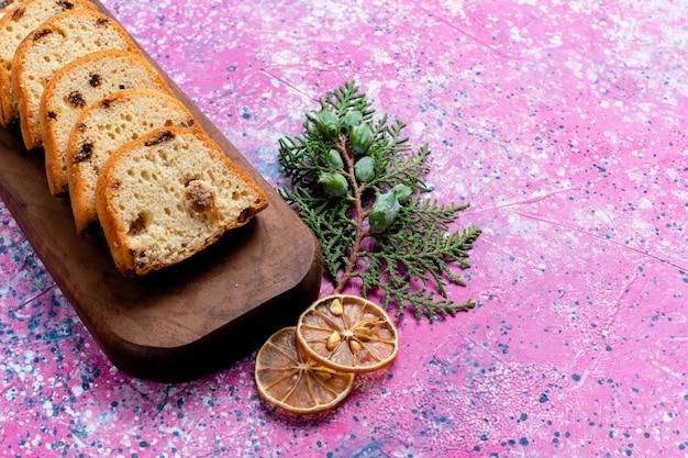전면보기 맛있는 건포도 케이크 분홍색 표면에 파이 슬라이스 파이 설탕 달콤한 비스킷 쿠키
