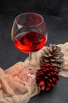 Front view of delicious red wine in a glass goblet on towel and conifer cones on a dark background