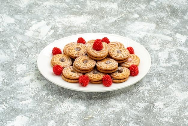 Vista frontale deliziosi biscotti rotondi con confetture di lamponi su uno spazio bianco